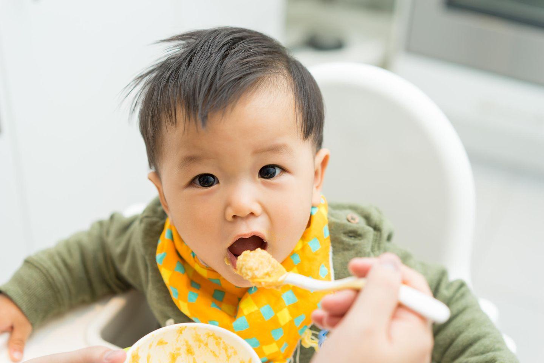 Ein Baby sitzt im Hochstuhl und wird mit einem Löffel Beikost gefüttert