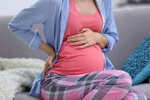 Eine Schwangere hat Übungswehen, sitzt auf der Couch und hält ihren Bauch