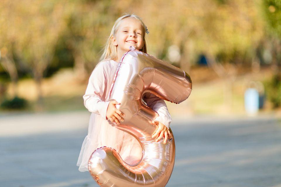 Glückliches kleines Mädchen hält eine große aufgeblasene 5 in den Armen