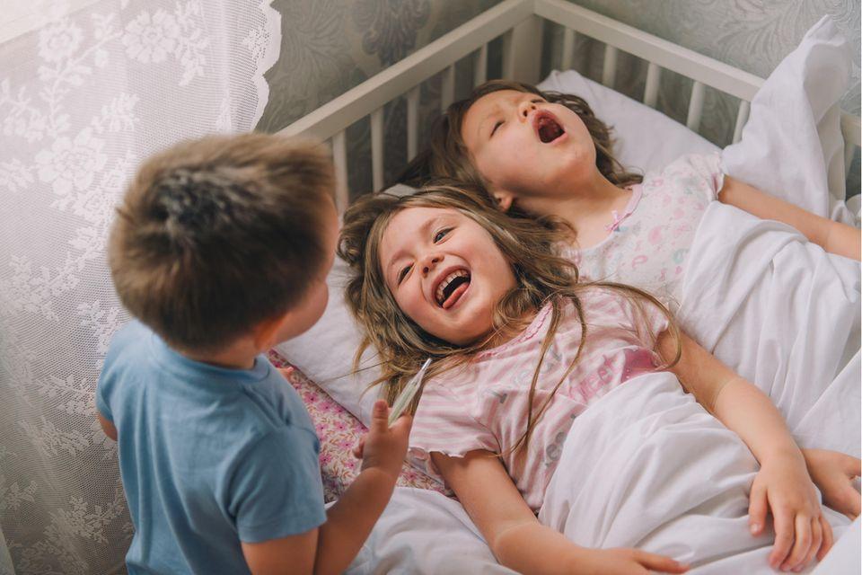 Drei kleine Kinder spielen Arzt und lachen