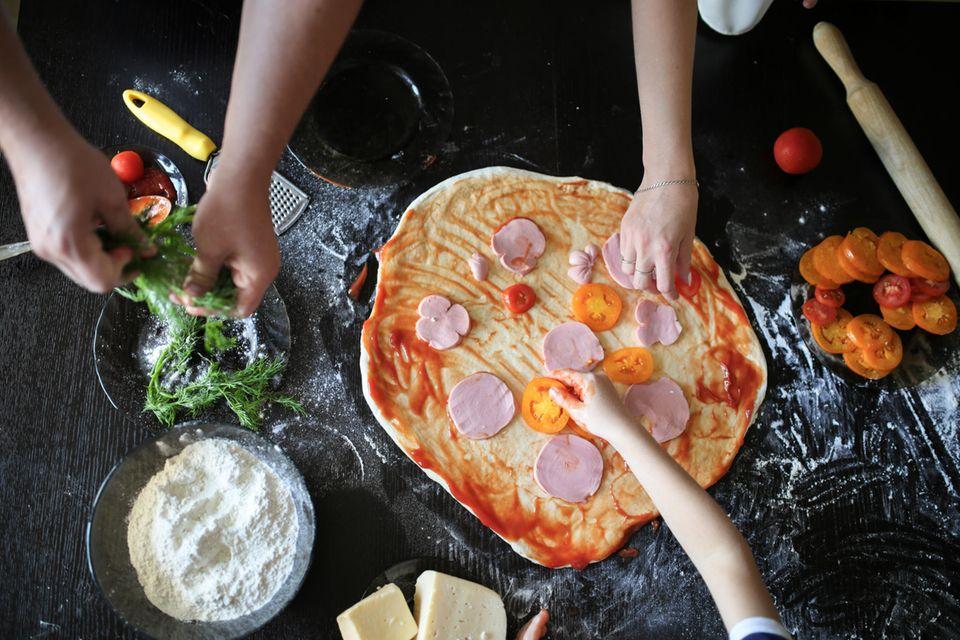 Eine große Pizza wird von Kinderhänden belegt