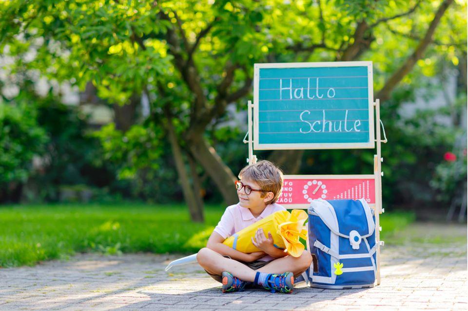 Einschulung: Junge mit Brille sitzt mit Schultüte und Schulranzen auf dem Schulhof.