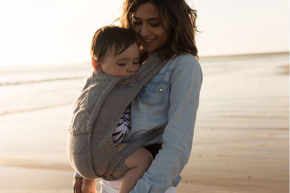 Junge Mutter spaziert mit schlafendem Kind in der Babytrage am Strand.