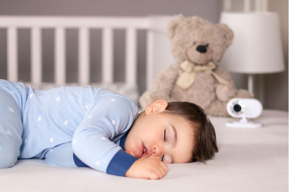 Schlafender Junge im Pyjama wird von Babyphone-Kamera im Bett bewacht.