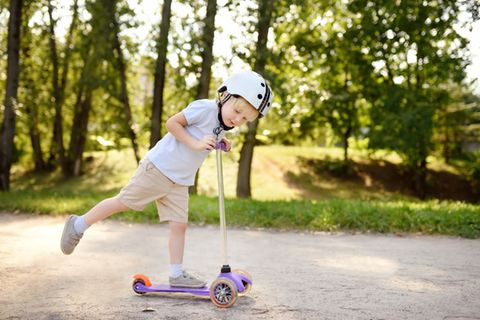 Kleiner Junge in kurzen Hosen und Helm testet einen Kinderoller im Park.