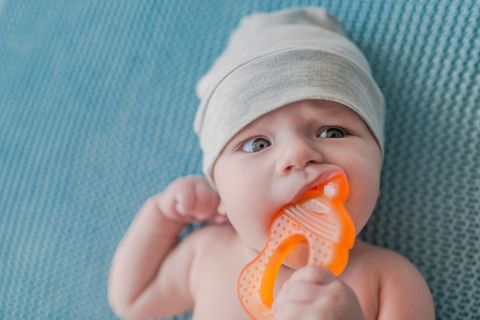 Verwundert schauendes Baby mit Mütze kaut auf seinem Beißring herum.