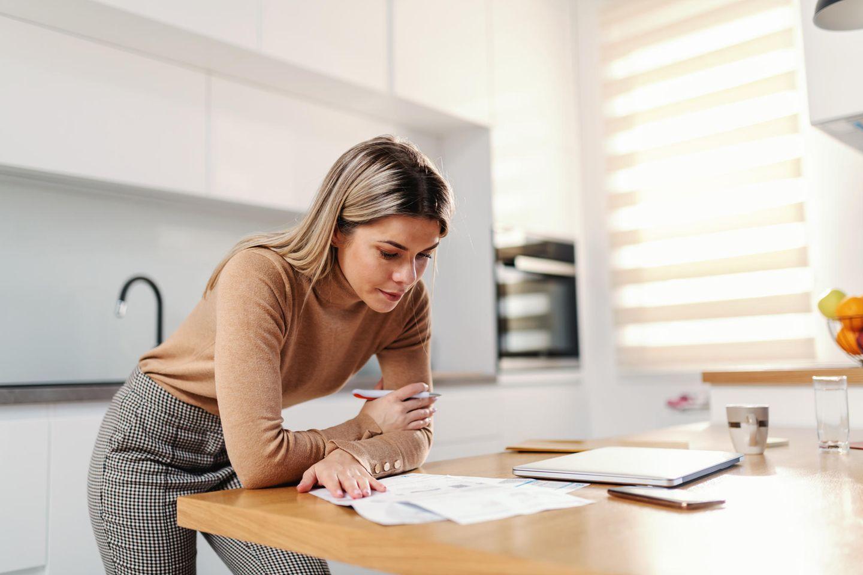 Frau rechnet am Küchentisch Finanzen durch