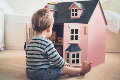 Rosa ist für alle da: Kind spielt mit Puppenhaus