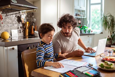 Vater mit Sohn machen Schulaufgaben
