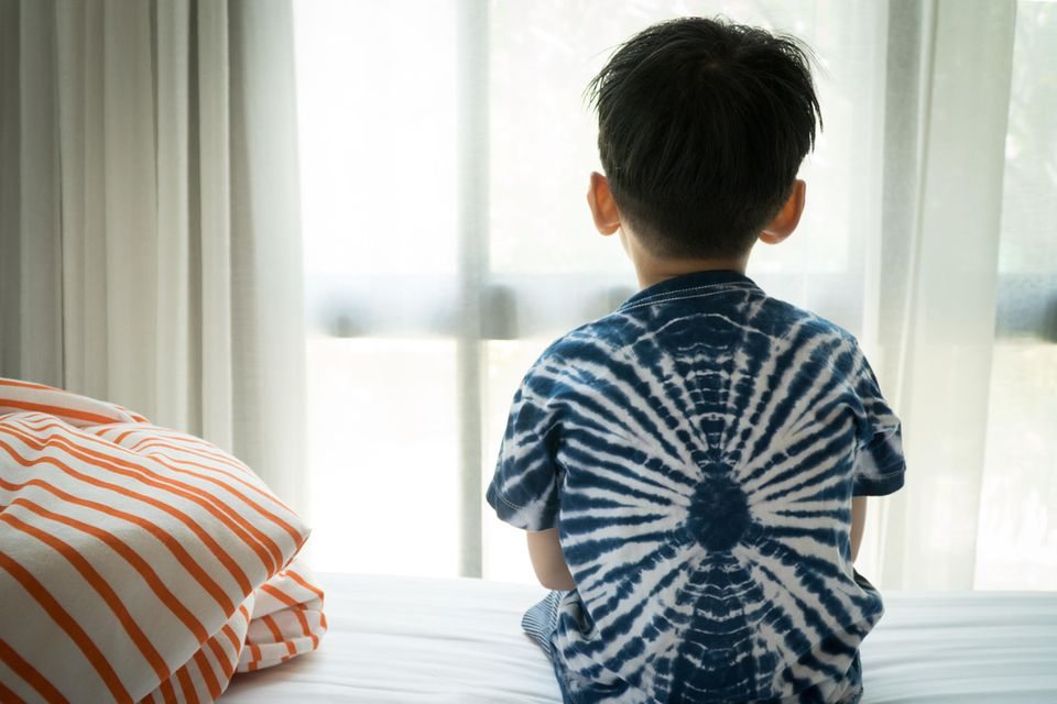 Kinderärzte warnen: Junge sitzt auf dem Bett