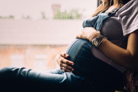 Dammmassage: Eine schwangere Frau sitzt auf einer Fensterbank