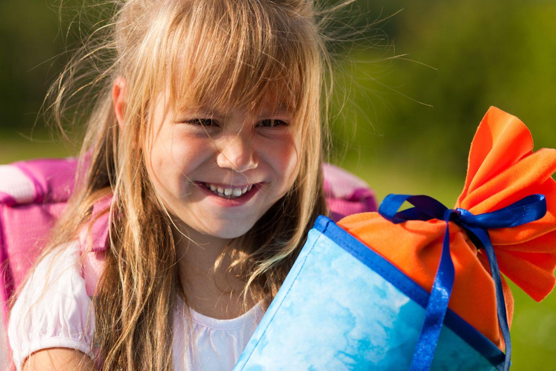 Geschenk zur Einschulung: Mädchen mit Schultüte und Schulranzen am ersten Schultag.