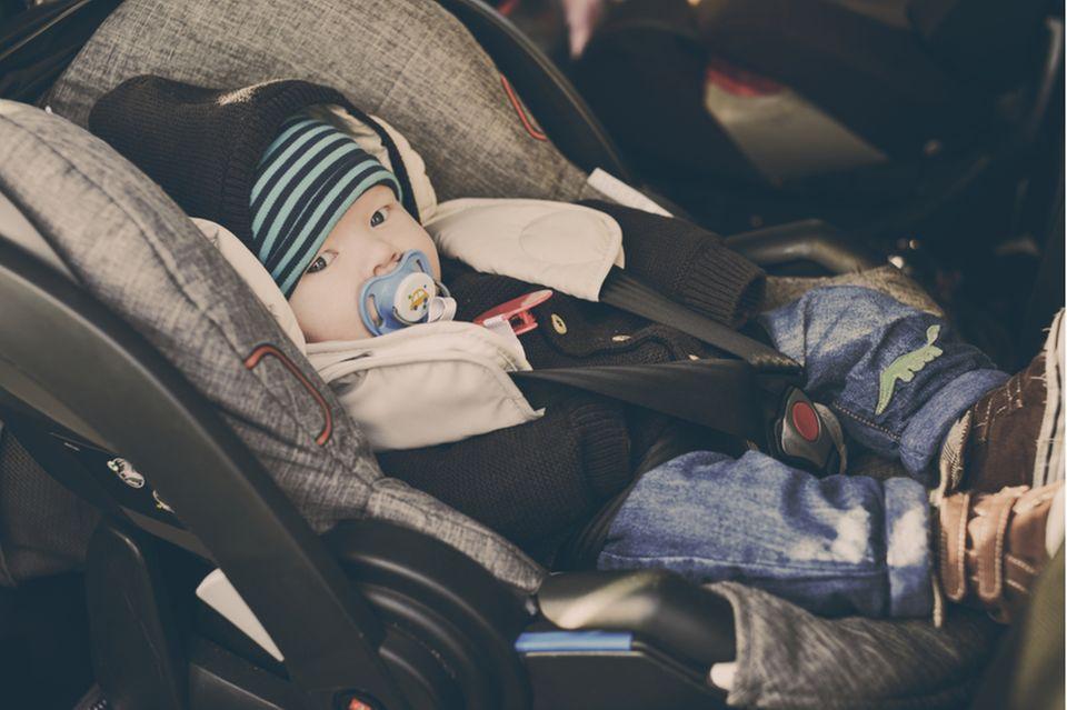 Babyschale im Test: Baby mit Mütze, Jacke und Schnuller sitzt angeschnallt in Babyschale.