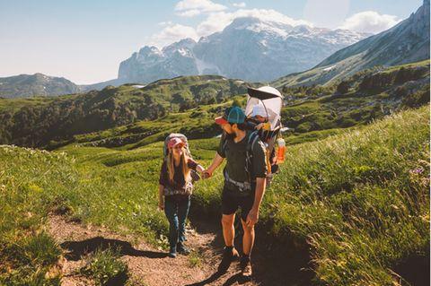 Kraxe im Test: Junges Paar wandert mit Baby in der Kraxe in sommerlicher Alpenlandschaft.