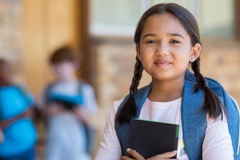 Selbstbewusst lächelnde Schülerin mit Rucksack und Buch