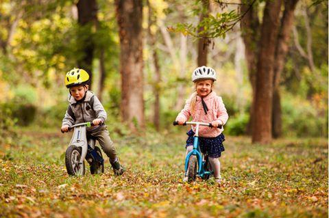 Laufräder im Test: Mädchen und Junge mit Helmen fahren fröhlich mit Laufräder auf einer Waldwiese.