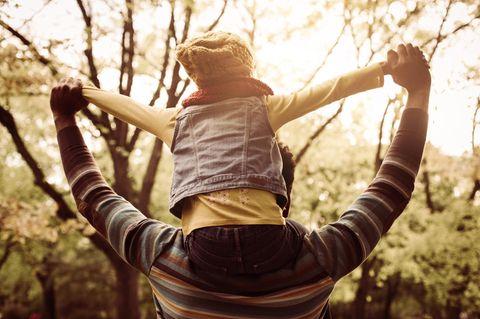 Sexuelle Orientierung thematisieren: Vater mit Kind auf den Schultern in der Natur