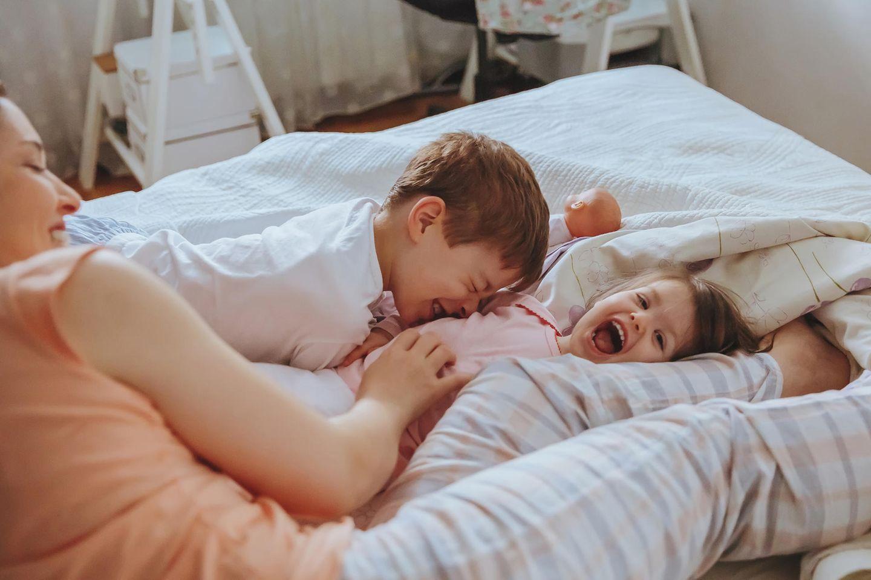 Kinder lachen mit Mama morgens im Bett