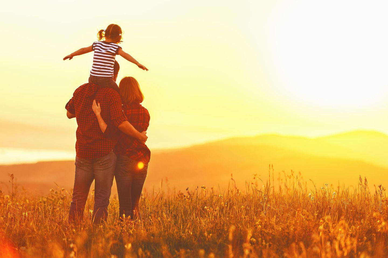 Vater mit Tochter auf den Schultern und Frau im Arm stehen mit dem Rücken zur Kamera, draußen