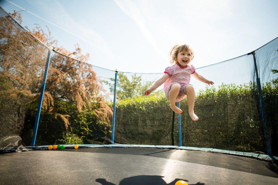 Gartentrampolin im Test: Kleines Mädchen hüpft auf Gartentrampolin mit Sicherheitsnetz.