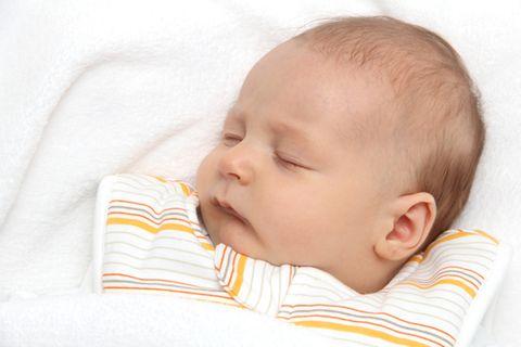 Im gestreiften Schlafsack schläft das Baby warm und sicher.