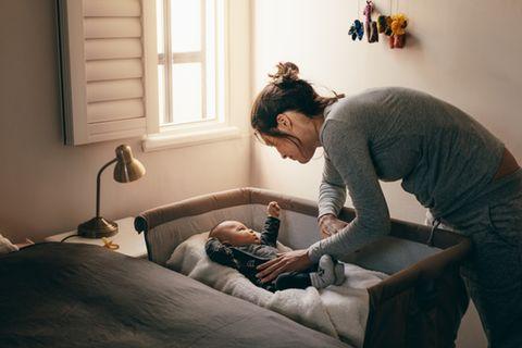 Junge Mutter beugt sich über Beistellbett um ihr Baby zu beruhigen.