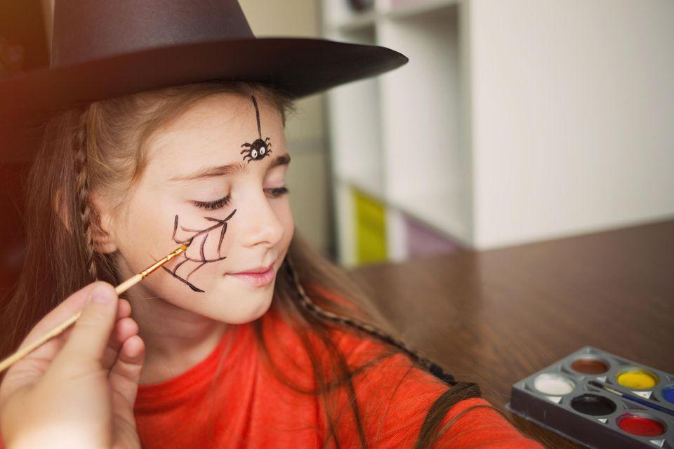 Hexe schminken: Kind mit Spinnennetz auf der Wange