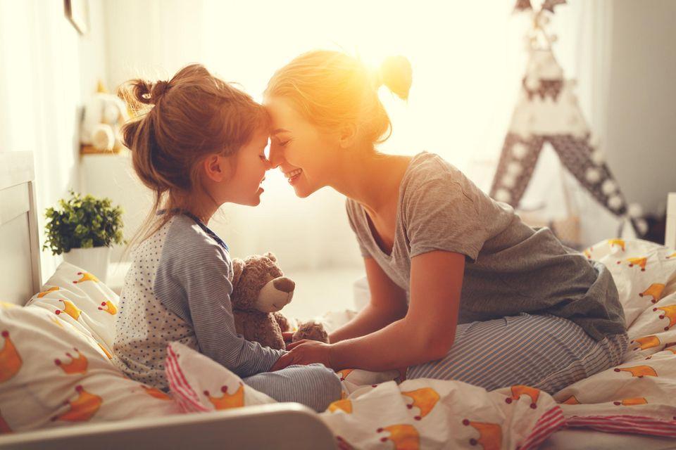 Horoskop: Mutter und Tochter sitzen im Bett
