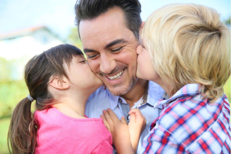 Vatertagssprüche: Papa mit zwei Kindern.