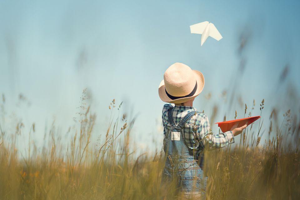 Papierflieger basteln: Kind mit Papierflieger in der Hand