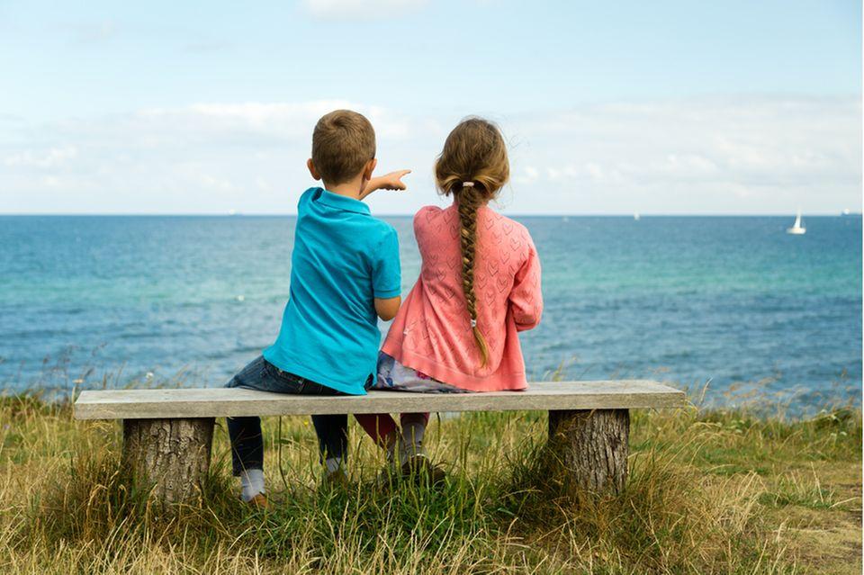 Nordische Namen: Mädchen und Junge auf einer Bank vor einem See.