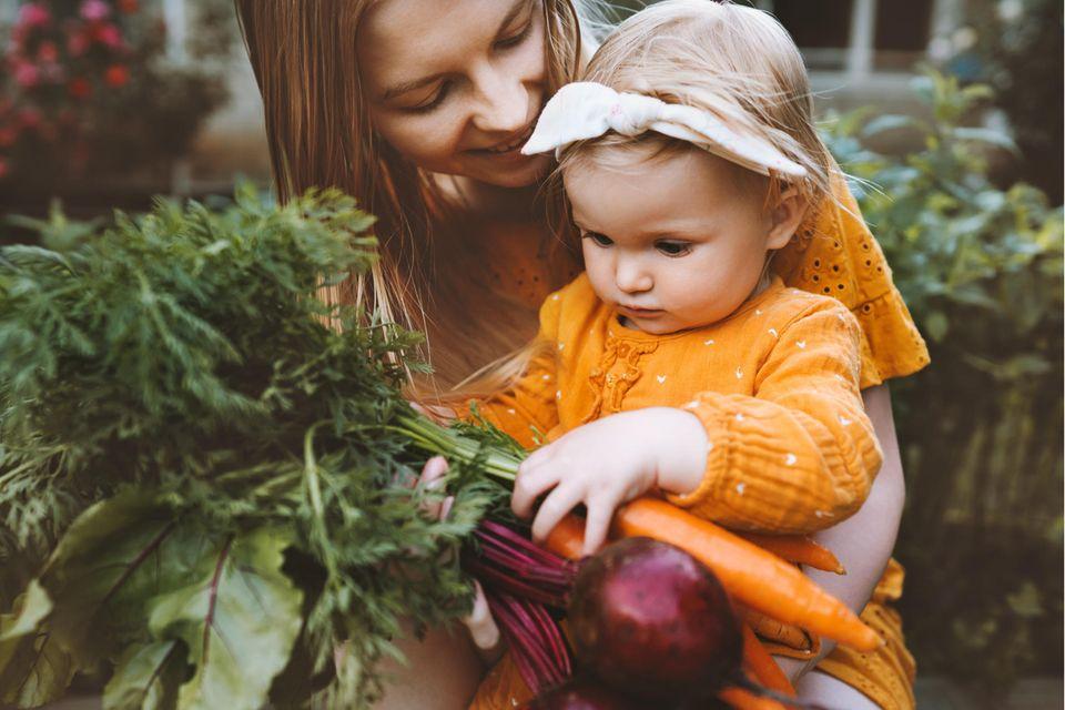 Mama und Kind kaufen regionales Gemüse ein