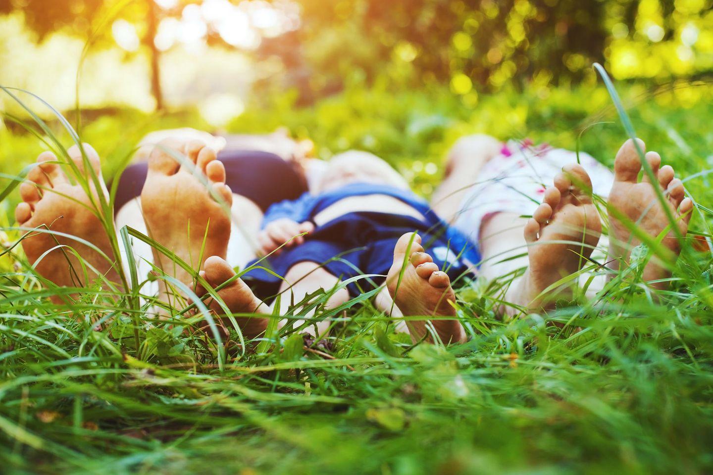Familie liegt barfuß im Gras