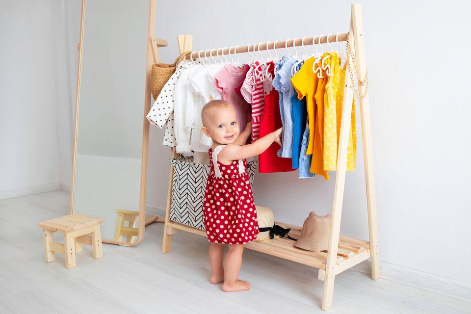 Baby steht vor ihrer Garderobe