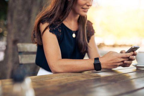 Frau mit Handy sitzt draußen in einem Cafe