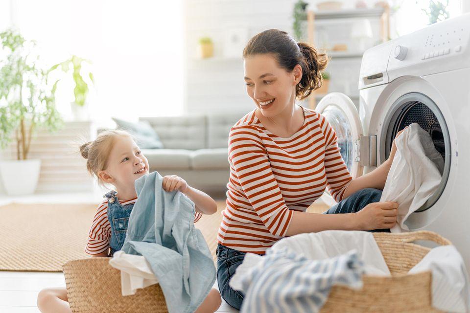Mama und Tochter waschen Wäsche