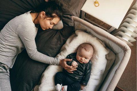 Reisebett im Test: Draufsicht auf schlafende Mutter mit Baby im Reisebett neben sich.