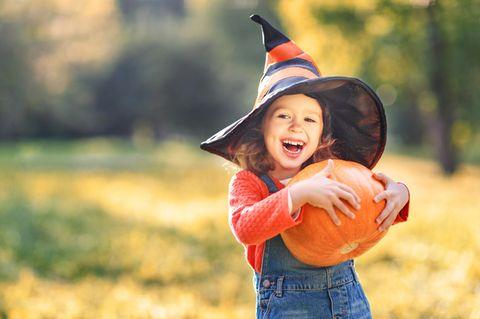 Mädchen mit Hexen-Hut hält einen Halloween Kürbis und lacht