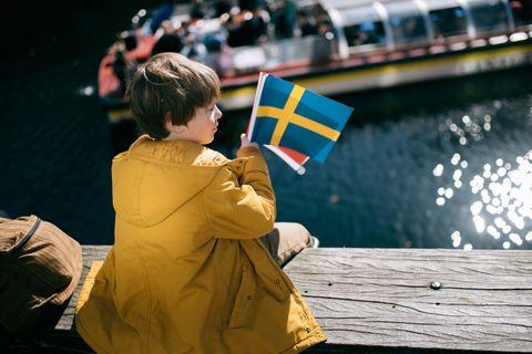 Nordische Jungennamen: Junge hält Schwedenflagge in der Hand.