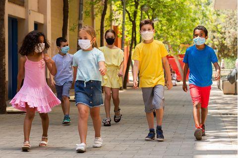 Kinder mit Masken verlassen die Schule