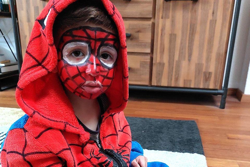 Kleiner Junge mit Spiderman-Kostüm und Make-up