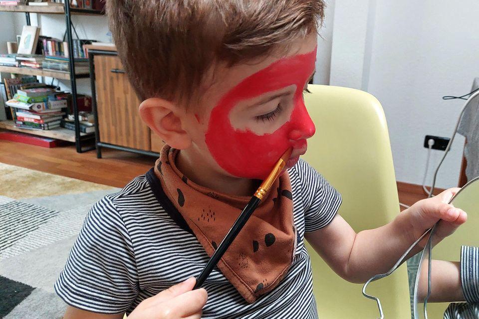 Kleiner Junge schminkt sein Gesicht wie Spiderman
