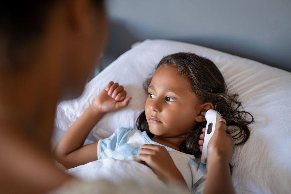 Ohrthermometer im Test: Fiebermessen bei einem Mädchen im Bett