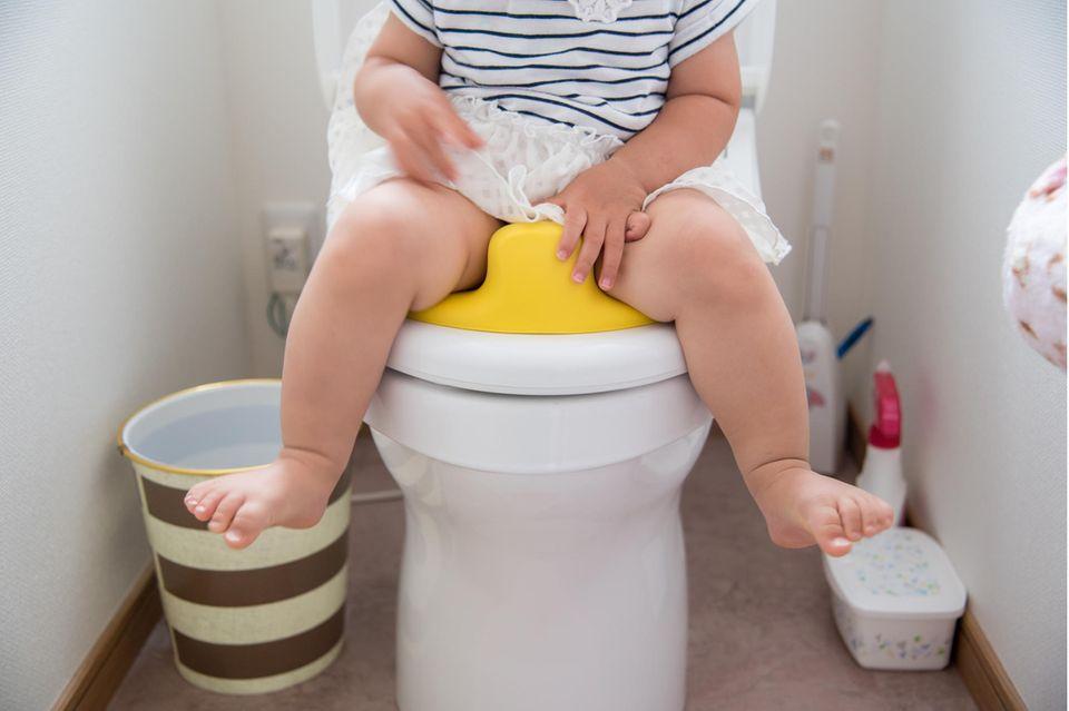 Toilettensitz für Kinder im Test: Ausschnitt eines Mädchens mit Rock auf dem Toilettentrainer