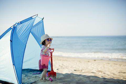 Strandmuschel im Test: Kleines Mädchen spielt im Zeltschatten am sonnigen Strand.