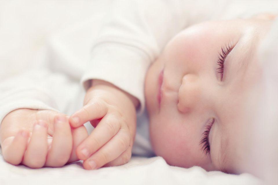 Babymatratze im Test: Friedlich schlafendes Baby in Weiß.