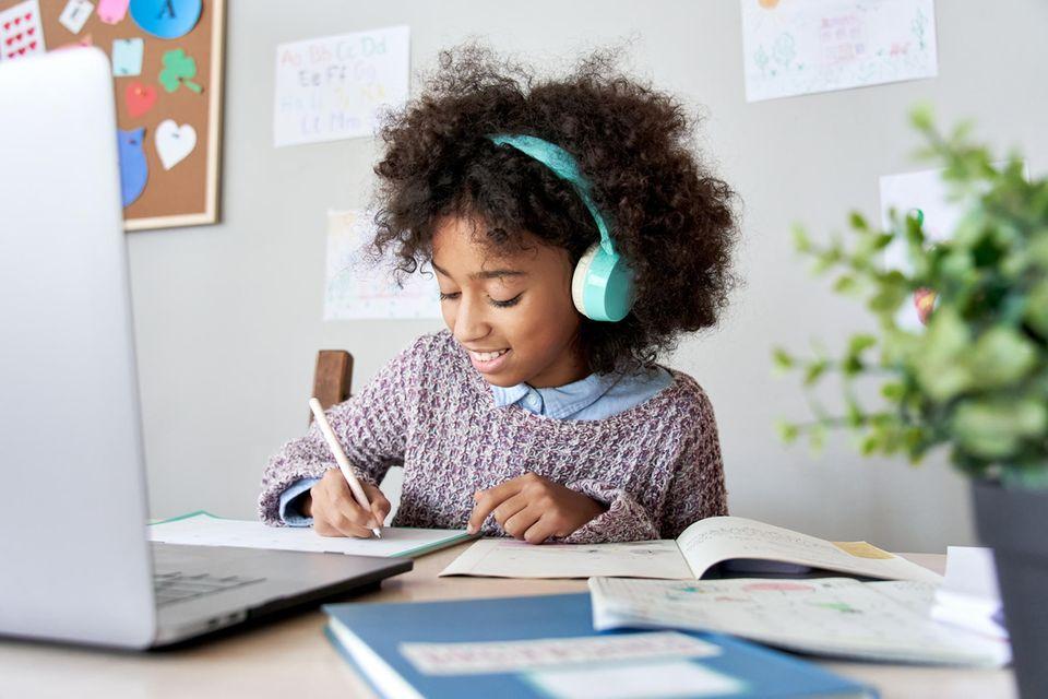 Kinderschreibtisch im Test: Lächelndes Mädchen mit  Kopfhörern macht Schulaufgaben am Tisch.