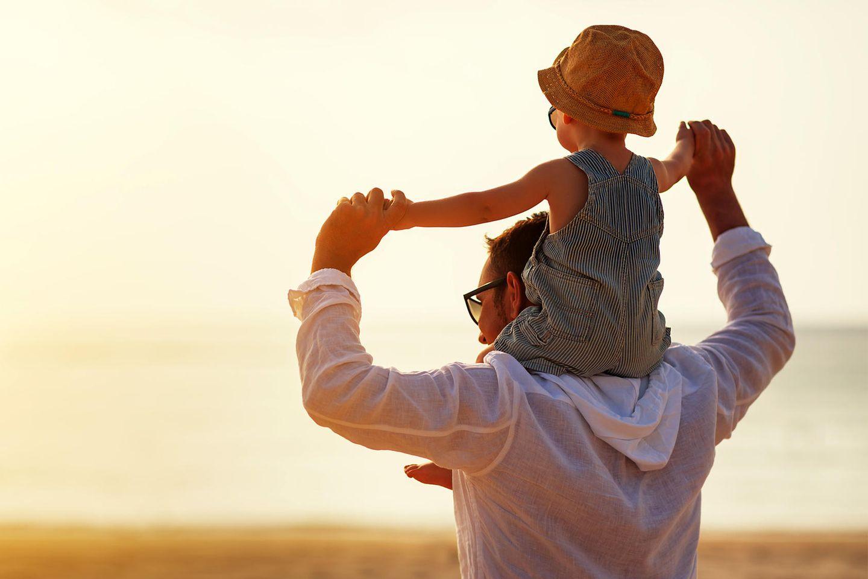 Rollentausch: Vater trägt Sohn auf den Schultern