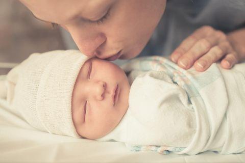 Geschenke zur Geburt: Frau küsst schlafendes Neugeborenes