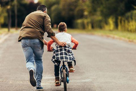 Erziehungsstil: Vater fährt mit Kind Rad